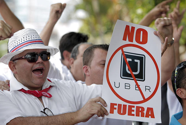 """A taxi driver holds a sign which reads """"No Uber, out"""", during a protest against car-sharing service Uber, outside the embassy of Colombia, in San Jose July 29, 2015. The drivers say that Uber, which local media reports is possibly launching in Costa Rica, is unfair competition. REUTERS/Juan Carlos Ulate"""